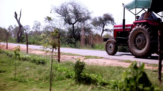 vídeos y material grabado en eventos de stock de tractor de granjero del montar a caballo en carretera - oficio agrícola