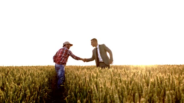 SLO MO Farmer shaking hands with an executive