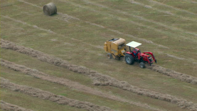 a farmer sits on a tractor with a hay baler in a field. - 干し草点の映像素材/bロール