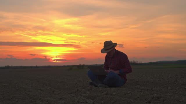 MS-Farmer sitzen, mit Laptop in idyllischer, ländlicher Gepflügtes Feld bei Sonnenuntergang