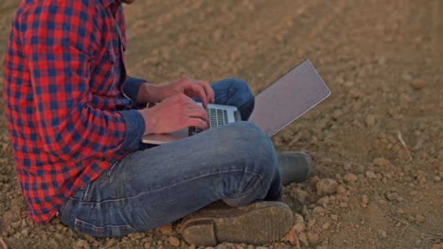 ms farmer sitting,using laptop in idyllic,rural plowed field - man sitting cross legged stock videos & royalty-free footage