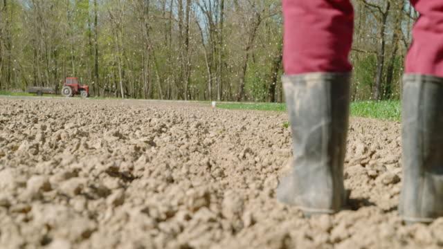 vídeos y material grabado en eventos de stock de slo mo granjero separarse fertilizante sobre un campo - potasio