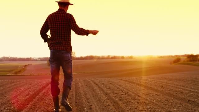 Boer verspreiden, langzame zaaien in idyllische, landelijke geploegd veld bij zonsondergang, motie