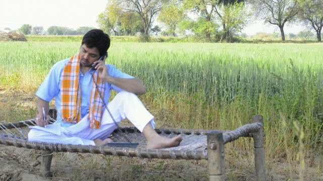 MS Farmer talking on landline phone while sitting on wooden bed near field at town / Gurgaon, Haryana, India