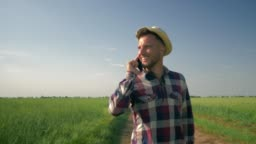 farmer talking on phone while walking on a country road, smiling man in hat and checkered shirt enjoy the fresh air and the beauty of nature on green