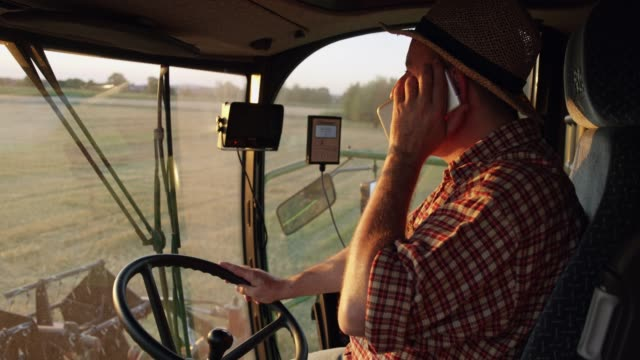 farmer talking on smart phone and driving combine harvester,slow motion - tractor stock videos & royalty-free footage