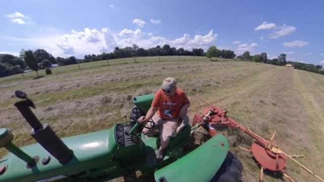 farmer tedding hay in the field - midday stock videos & royalty-free footage