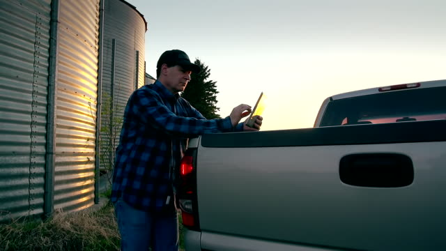 Farmer uses a digital tablet to access the internet