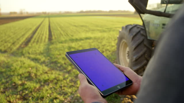 slo mo farmer using a digital tablet with chroma key background next to a tractor on the field - agriculture stock videos & royalty-free footage