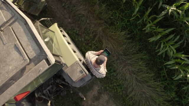 aerial farmer using a tablet beside a tractor parked on the edge of a field. - plaid shirt stock videos & royalty-free footage