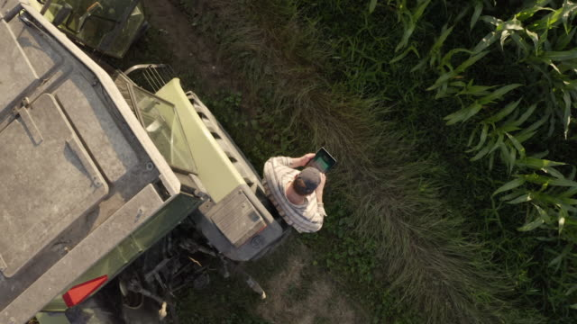 aerial farmer using a tablet beside a tractor parked on the edge of a field. - agriculture stock videos & royalty-free footage