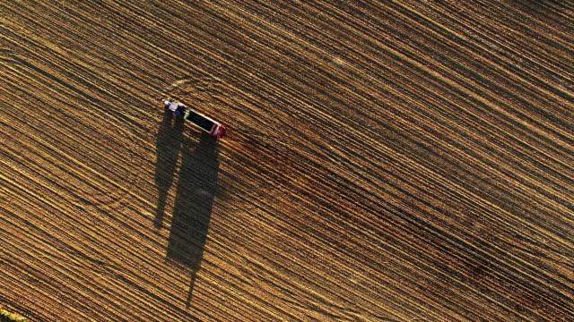 vídeos de stock, filmes e b-roll de agricultor aérea usando um trator para espalhar estrume sobre um campo - pulverizando
