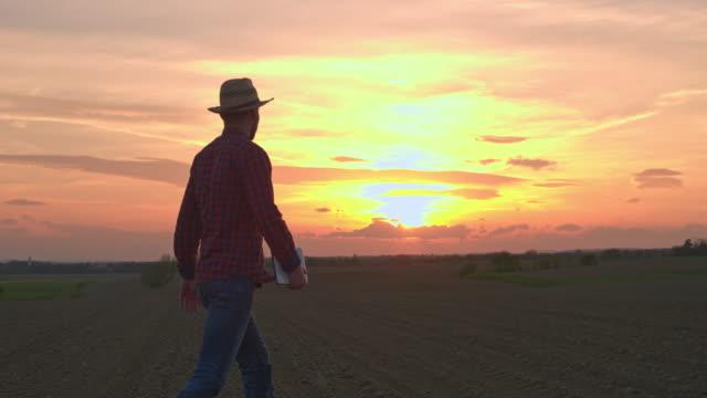 MS-Farmer mit digital-Tablette in idyllischer, ländlicher Gepflügtes Feld bei Sonnenuntergang