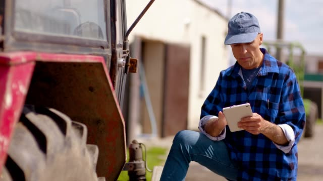 農学部附属農場トラクター、農業農家、品質管理、農家の農場で働いてに対してデジタル タブレットを使用して農家 - 農学者点の映像素材/bロール