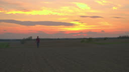 WS Farmer walking in idyllic,rural plowed field at sunset