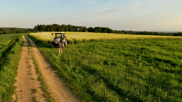 aerial slo mo farmer walking to a tractor - tractor stock videos & royalty-free footage