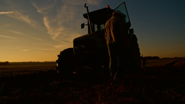 WS Farmer with a tractor at sunset