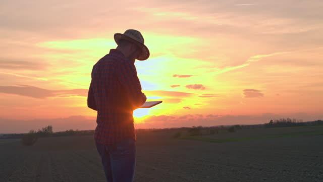 MS-Farmer mit digital-Tablette im idyllischen, ländlichen Gepflügtes Feld bei Sonnenuntergang