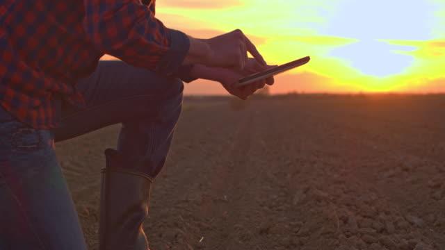 MS-Farmer mit digital-Tablette schöpfen und Prüfung Schmutz im ländlichen Gepflügtes Feld bei Sonnenuntergang