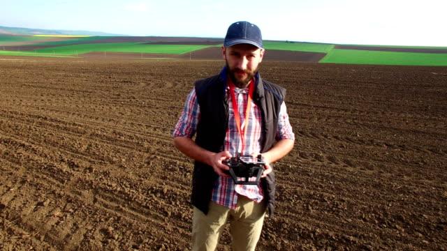 剥かれたフィールドにドローンと農夫 - 農学者点の映像素材/bロール