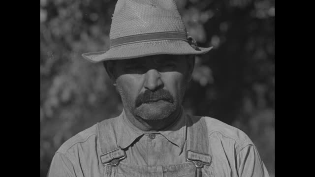 vidéos et rushes de farmer with mustache wearing straw hat and overalls / note: exact day not known - moustache