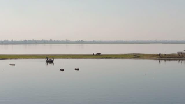 farmer with ox cart and fishing boat in amarapura, myanamar - spoonfilm stock-videos und b-roll-filmmaterial