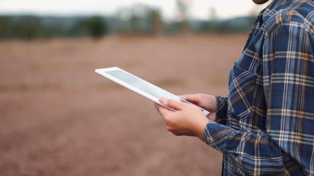 vídeos de stock, filmes e b-roll de mulher do fazendeiro com a tabuleta digital que verific o solo orgânico agricultura campo do arroz campo de trigo do terraço durante uma estação seca do verão - internet das coisas