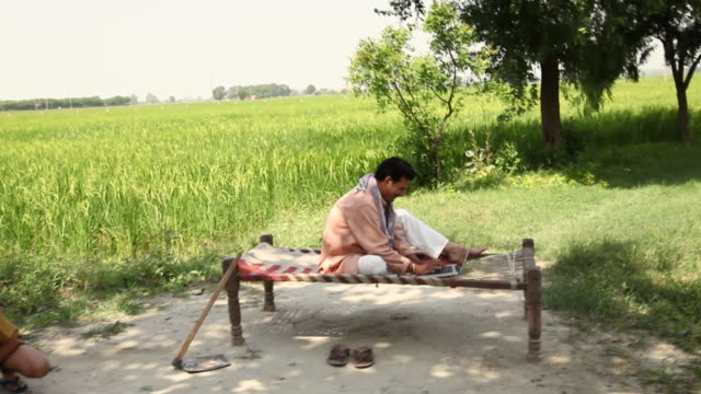 farmer working on a laptop with his children playing  - dhoti video stock e b–roll
