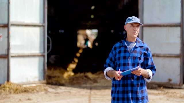 farmer working on farm while looking around. - farmhouse stock videos & royalty-free footage