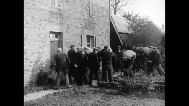 dramatization farmers attacking town official farmers stacking bags of grain outside official's door night male legs amp feet slipping into wooden... - 1934 stock-videos und b-roll-filmmaterial