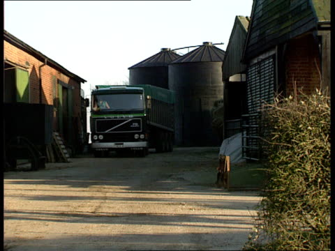 bse compensation payouts ext lorry pulls out of farmyard / forklift truck lifting bales of hay / cows in stall / forklift deposits bales of hay next... - hay truck stock videos & royalty-free footage