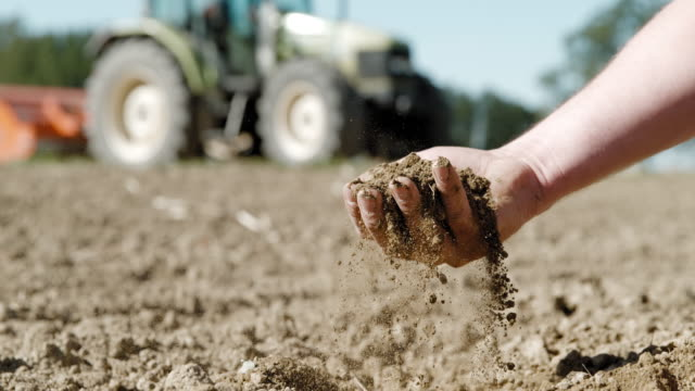 SLO MO Farmer's hand scooping dirt on a field