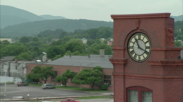 HA MS ZO WS Farmers Market with surrounding buildings, clock tower, parking lot and hills in background / Rutland, Vermont, USA