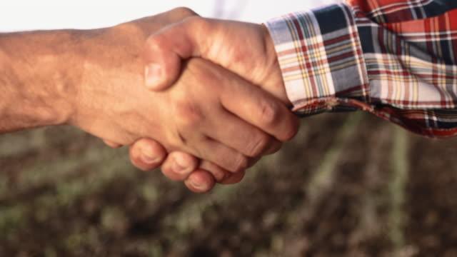 CU boeren schudden van handen in het veld