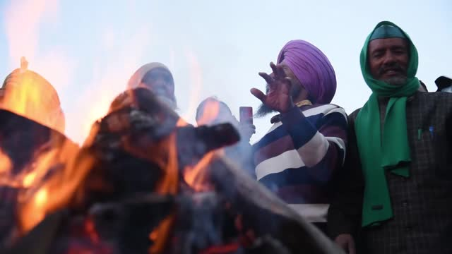 farmers shout slogan against indian prime minister narendra modi as they celebrate the lohri festival, at the site of farmers protest against the new... - punjab region stock-videos und b-roll-filmmaterial