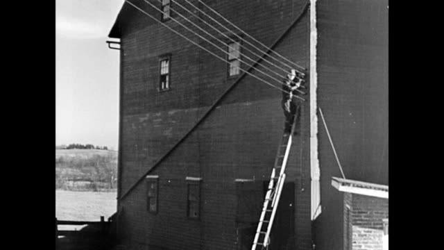 farmers stand at the bottom of pylon reading one meter / man on side of house reading another electric meter farm cooperative members read electric... - agricultural cooperative stock videos and b-roll footage