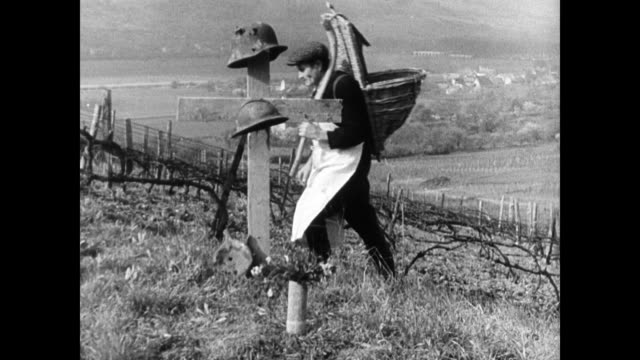 farmers w/ shoulder baskets walking up hill passing christian cross grave marker holding wwi helmets peasant woman knitting next to in home memorial... - root vegetable stock videos and b-roll footage