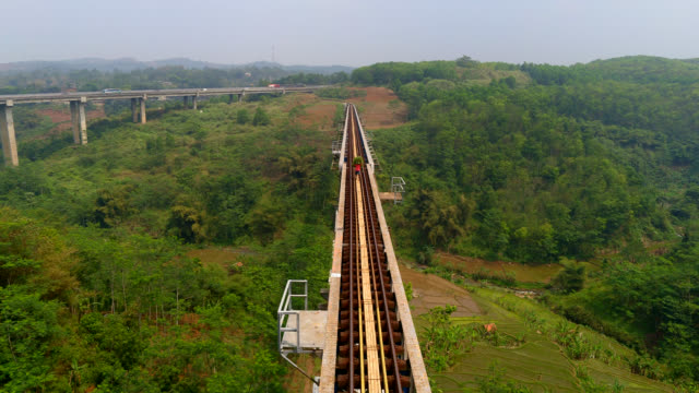farmers walking at cikubang rail bridge - indonesia stock videos & royalty-free footage