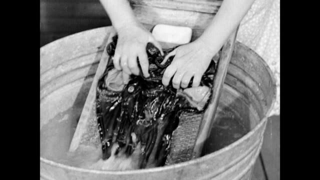 vídeos de stock e filmes b-roll de farmer's wife hazel parkinson boils water on wood stove for laundry / hazel scrubs clothes in wash tubs as her daughter cleans the oil lamps /... - donos de casa