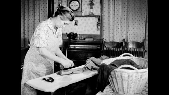 stockvideo's en b-roll-footage met farmer's wife ironing with stove heated iron / sun sets and she lights the oil lamp and stokes the wood stove housewife irons clothes without... - strijkijzer