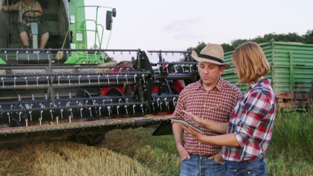 Los agricultores con digital tablet apretón de manos por cosechadora, cámara lenta