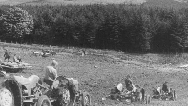1942 montage farmers working and fertilizing fields using shared mechanized equipment / united kingdom - 1942 stock videos & royalty-free footage