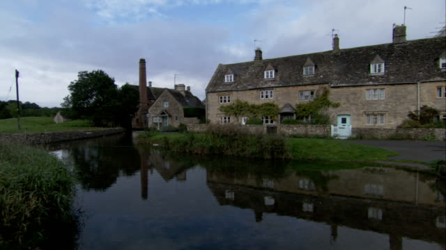farmhouse refelected in a pond in gloucestershire, england. available in hd. - gloucestershire stock videos and b-roll footage