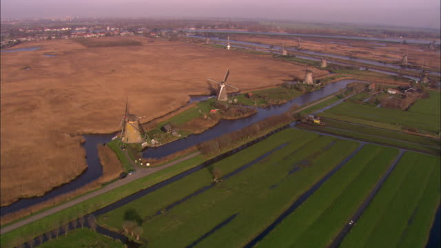 farmland surrounds windmills in a rural area. - netherlands stock videos & royalty-free footage