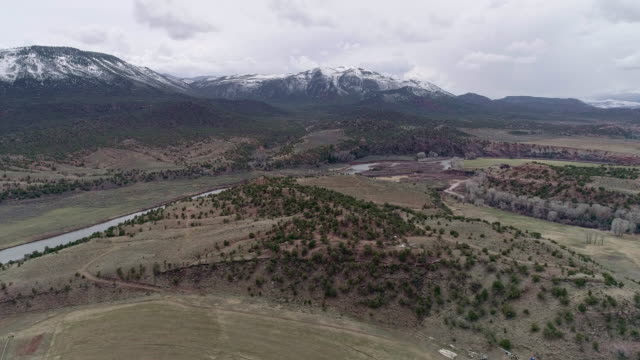 vídeos de stock e filmes b-roll de farmlands in colorado mountains, nearby mccoy, and colorado river, in the early spring. aerial drone video with the panoramic and descending camera motion. - rancho quinta