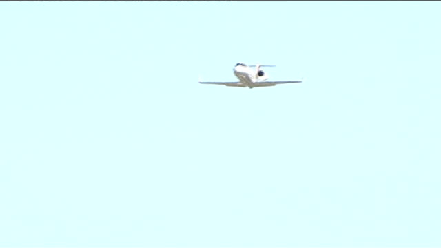 vídeos de stock e filmes b-roll de f1 car races lear jet down runway england hampshire farnborough ext red arrows display team flying across trailing red white and blue smoke / learjet... - farnborough hampshire