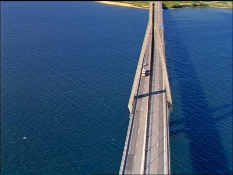 AERIAL Faro Bridge with Shell Oil trucks going over water / Falster, Denmark