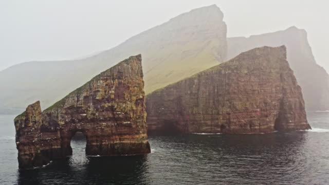 faroe islands drangarnir rocks in the rain drone flight 4k - north atlantic ocean stock videos & royalty-free footage