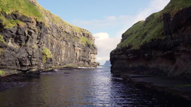 faroe islands gjogv natural harbor rock crevice gjógv eysturoy island 4k - north atlantic ocean stock videos & royalty-free footage