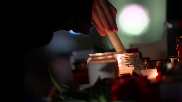 far-right terrorist kills nine people in shootings at hanau shisha bars; germany: hanau: ext / night woman lighting candles at vigil for victims of... - gedenkveranstaltung stock-videos und b-roll-filmmaterial